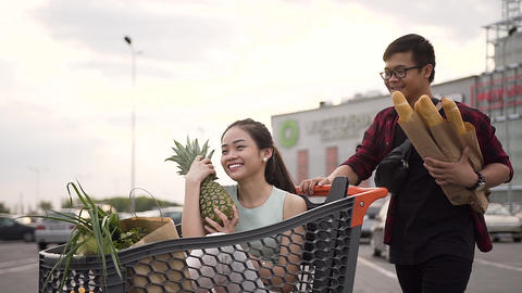 Likable young asian woman sitting in the shopping trolley with paper bags which Live Action