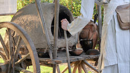 Life in medieval village. Woman is taking out bread from medieval dome oven Footage