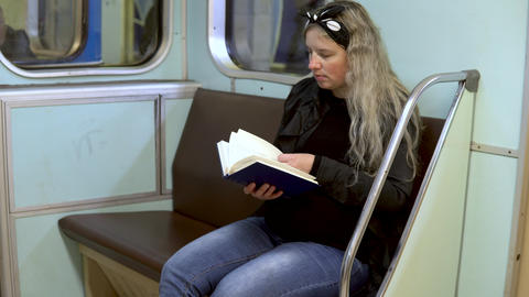 A pregnant woman is reading a book in a subway train. Old subway train car Live Action