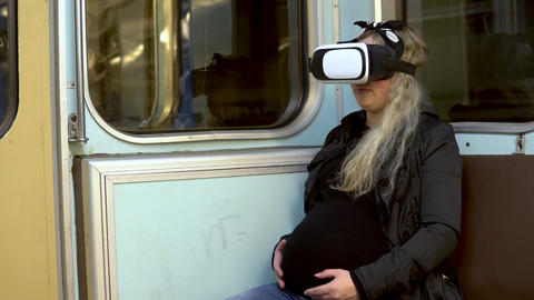 Pregnant woman in virtual reality helmet in subway train. Old subway train car Live Action