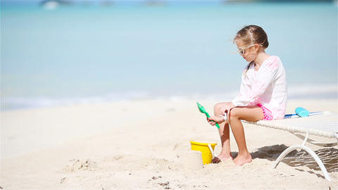 Adorable little girl playing with toys on beach vacation. Kid play with sand Live Action