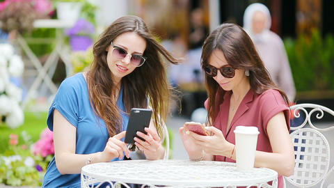 Two young girls using smart phone at the outdoors cafe. Two women after shopping Live Action