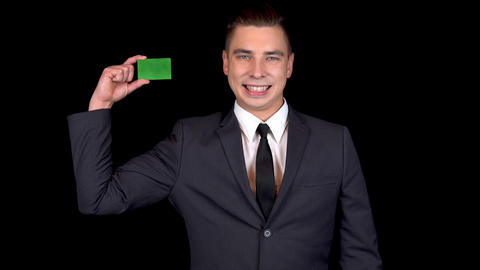 A young businessman presents a green bank card. Chromakey green card. Man in a Footage