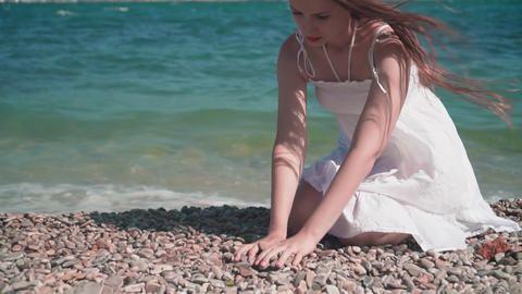 A girl in a white beach dress, sits on a rocky seashore. A beautiful girl sits Live Action