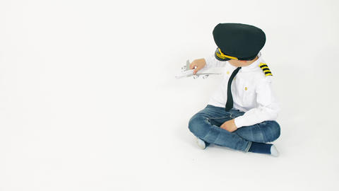 Boy wearing pilot's uniform plays with toy commercial airplane. Aircraft landing Live Action
