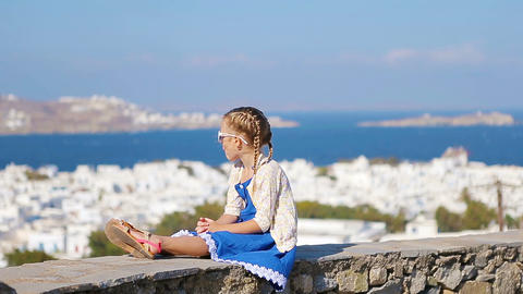 Portrait of adorable little girl background Mykonos town in Europe Live Action