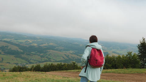 Lady hiker with backpack looking on hills and mountains Footage