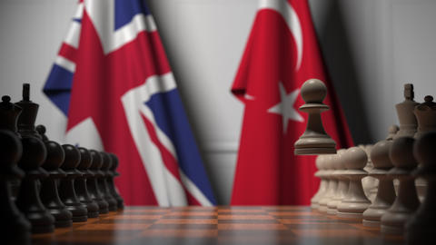 Chess game against flags of Great Britain and Turkey. Political competition Live Action
