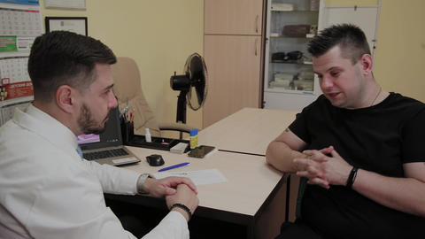 Male patient tells doctor about his health problems at the reception Footage