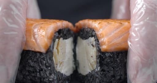 Chef splits in a half the sushi roll with black rice and salmon, cooking the raw Footage