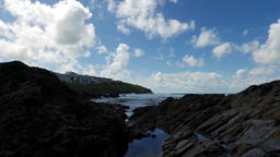 Gentle upward pan over coastal devonian rock rockpools to reveal lapping waves o Footage
