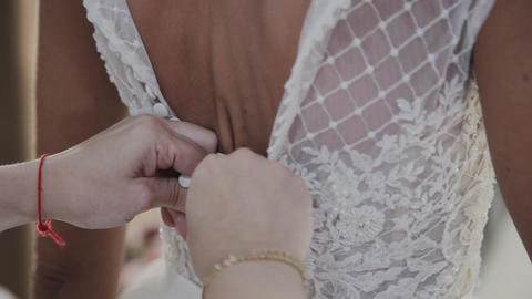 Close-up of the bridesmaid's hand buttoning the dress. Buttoning bride wedding Live Action