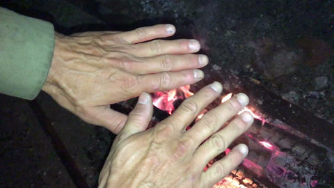 Neanderthal man warms his hands by the first bonfire in his cave Live Action