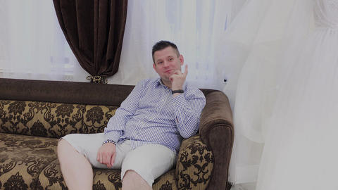 An emotional man sits on a sofa in a wedding salon and reacts to dresses that Live Action