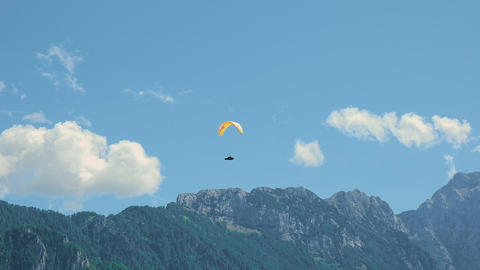 Flying in the mountains, paraglider in Alpine landscape, freedom and adventure Live Action