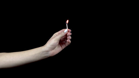 A woman holds a burning match while a man puts out a match with his fingers. 4k Live Action
