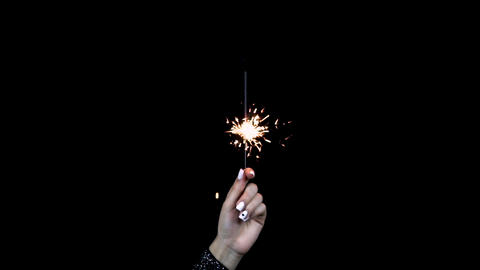 The girl holds a sparkler in a hand. The sparkler went out. Black background Footage