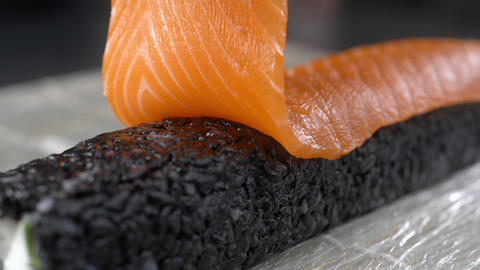Chef raw salmon to the black rice roll and makes sushi, cooking the raw red fish Live Action