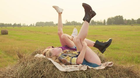 Girl teenager lying on haystack and swaying legs. Happy teenager girls moving Footage