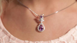 Silver pendant with a magenta diamond.Pretty girl's neck.Shallow depth of field Footage