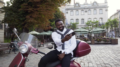 Attractive cheerful african american guy sitting on the fashion scooter and Footage