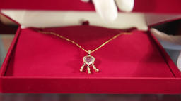 Hand in white glove opens red velvet jewelry box with silver pendant with Live Action