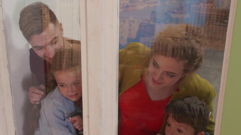 Family stand over the window and look out the window Footage
