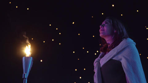 Woman watches as sky lanterns fly Into the night sky Live Action