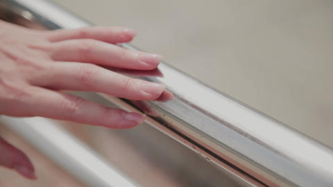 Woman hands on steel fence. Close up of woman manicured hands on metalic railing Footage