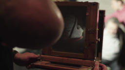 Ambrotype: A photographer takes a photo on a vintage camera in a studio Archivo