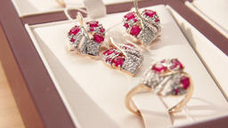Jewellery.Gold earrings with magenta heart-shaped diamonds at the jewelry store Live Action