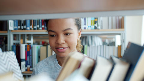 Portrait of attractive mixed race lady choosing books on shelf in bookshop Footage