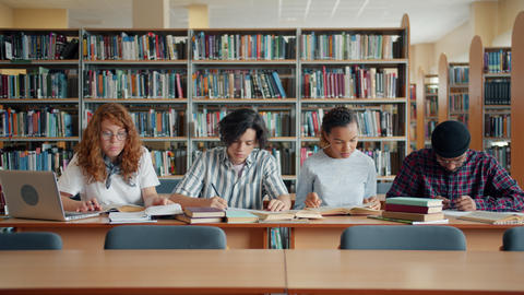 Portrait of busy youth students studying in library reading books writing notes Live Action