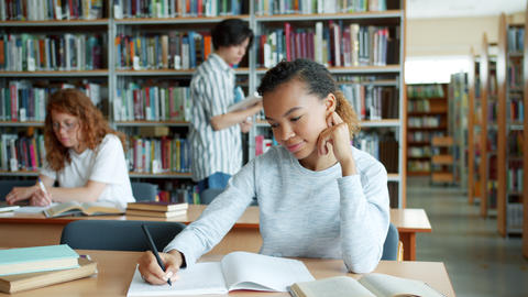 Mixed race student studying in library while other people learning in background Live Action