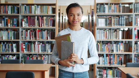 African American lady standing in library with books smiling looking at camera Footage
