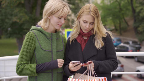 Two beautiful blond girlfriends standing on the street with their purchases in Live Action