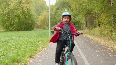 Happy teenager boy riding on bicycle in autumn park. Bicyclist boy cycling front Live Action