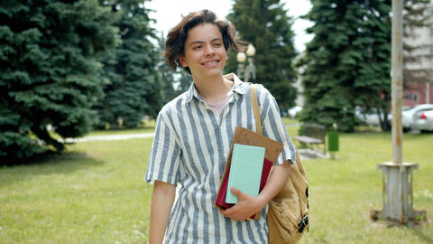 Cheerful guy walking outdoors in park waving hand greeting friends holding books Footage