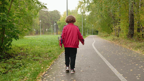 Little boy walking on pathway in summer park while beginning rain. Rear view Live Action