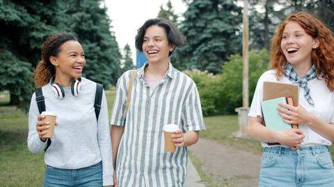 Joyful youth laughing having fun walking outdoors with books and to go coffee Live Action