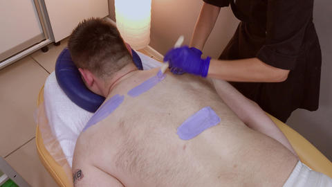 Professional beautician makes waxing to a man in a beauty parlor Live Action