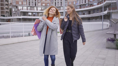 Two happy caucasian girls walking with shopping bags. Two fashion women chatting Live Action