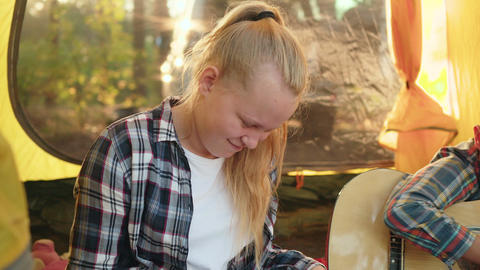 Teenager girl writing song to guitar music in camping tent. Boy teenager playing Footage