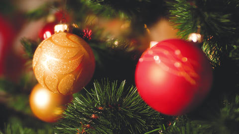 Closeup toned video of red and golden baubles on CHristmas tree with glowing and Footage