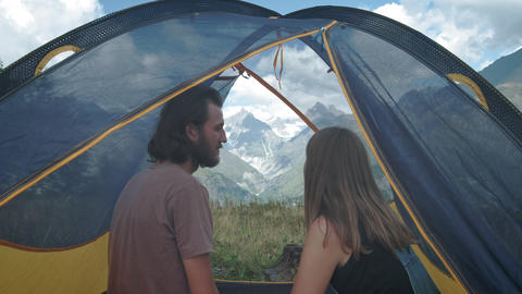 Couple of man and woman travelers kiss in a tent. Honeymoon on a camping trip. A Footage