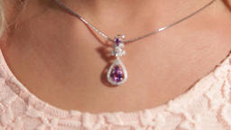 Beautiful female neck, on it is a silver pendant with a magenta diamond Live Action