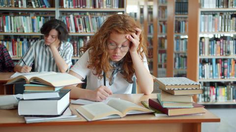 Slow motion of sleepy lady working in library then sleeping head on desk Footage