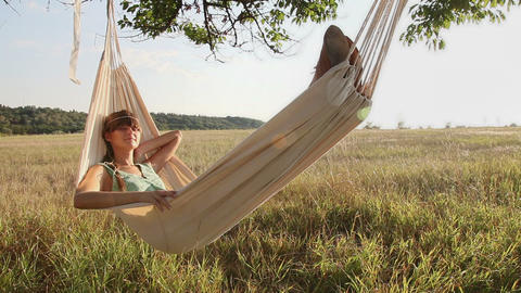 Pretty young girl swinging on hammock at sunset Stock Video Footage