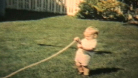 Boy Plays With Garden Hose 1963 Vintage 8mm Film stock footage