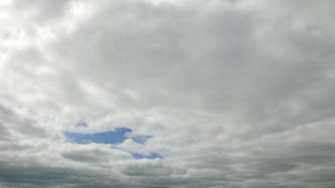 Clouds gather to solid cloudscape, quickly move away, time lapse shot Footage